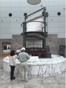 Ms. Narusawa and Mr. Yoshino at the cylindrical loom in the foyer of the Museum of Technology.