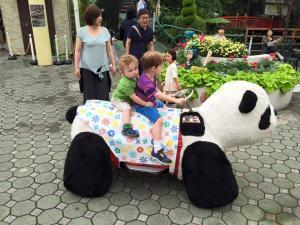 My kids (in June 2015) riding the famous coin operated giant pandas, while escorted by one of our new Japanese friends.