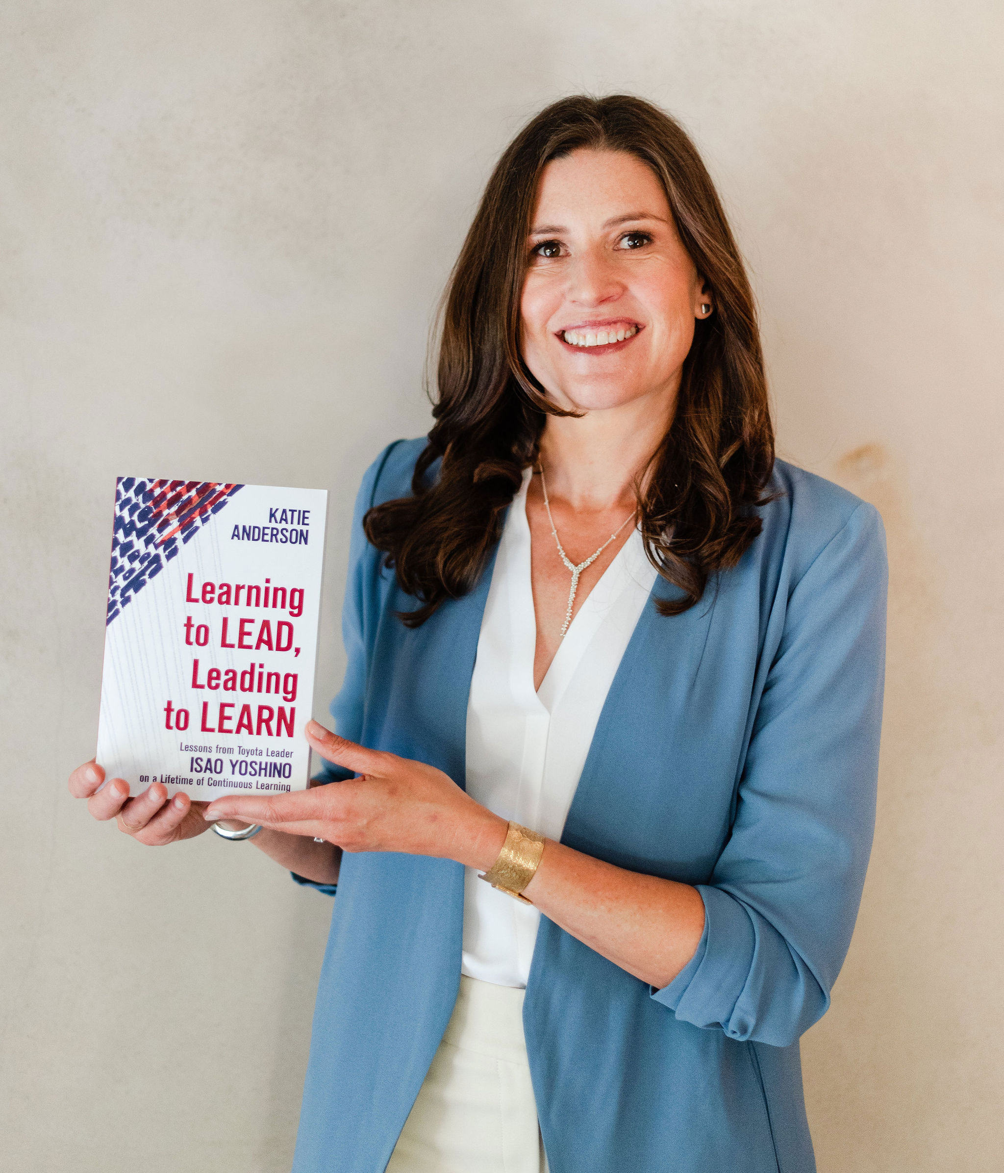 Katie Anderson holding the book on Leading to Learn Accelerator